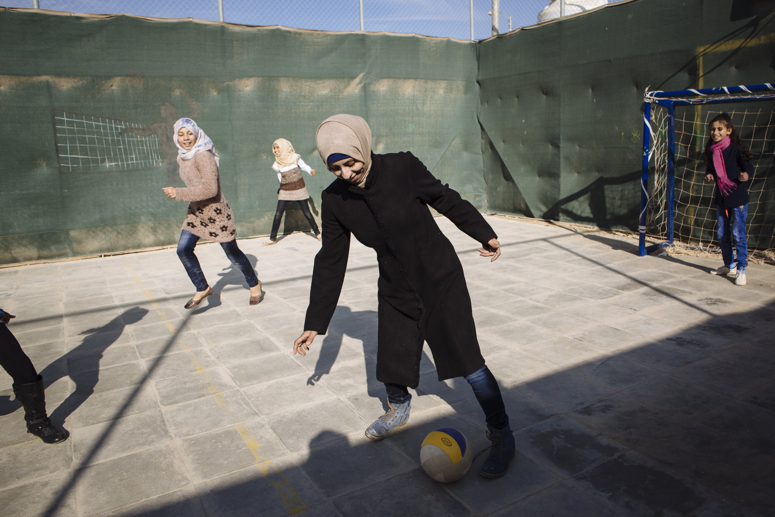 Syrian refugee and coach Nawar,  29, centre, controls the ball as she plays football with her students Amneh, 12, left, Ariam, 12, back left, and Muna, 12, right, at the International Relief and Development (IRD) compound in Za'atari refugee camp, Mafraq Governorate, Jordan.