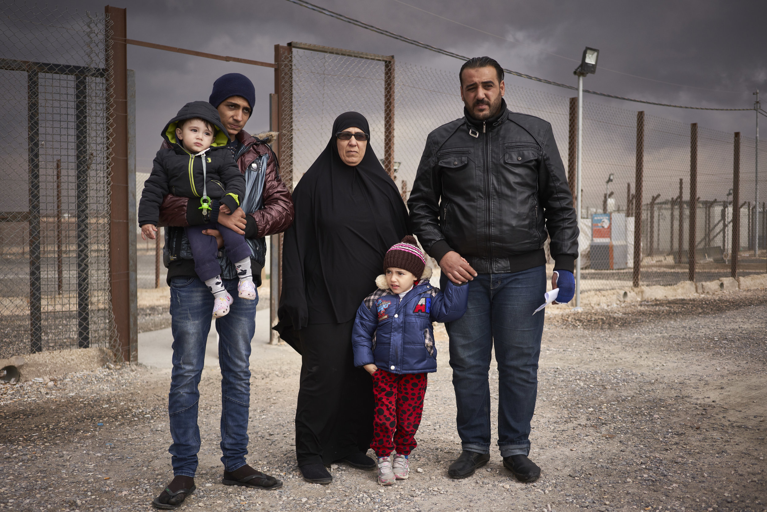 From right, Syrian refugee Marseel, 30, his daughter Yaucot, 5, mother Al Fareeda, 50, brother Yusuf, 14, and son Mohamed, 18 months, pose for a photograph before getting into a vehicle which will transport them to their newly assigned shelter in Azraq refugee camp, Zarqa Governorate, Jordan.