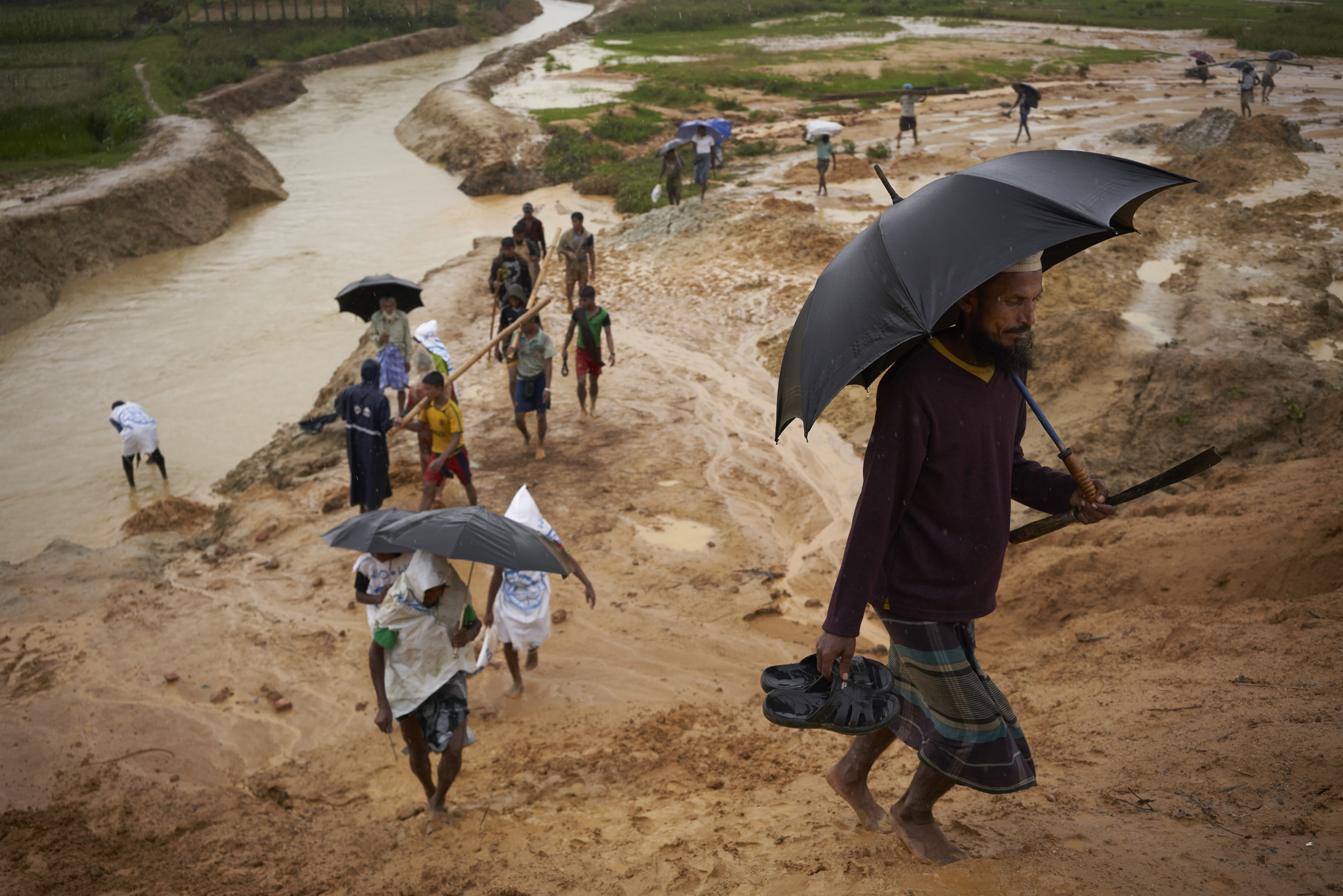 Rohingya refugees walk up an embankment leading to a road undergoing improvement work, in Kutupalong Expansion Site for Rohingya refugees, Ukhia, Cox's Bazar District, Bangladesh.
