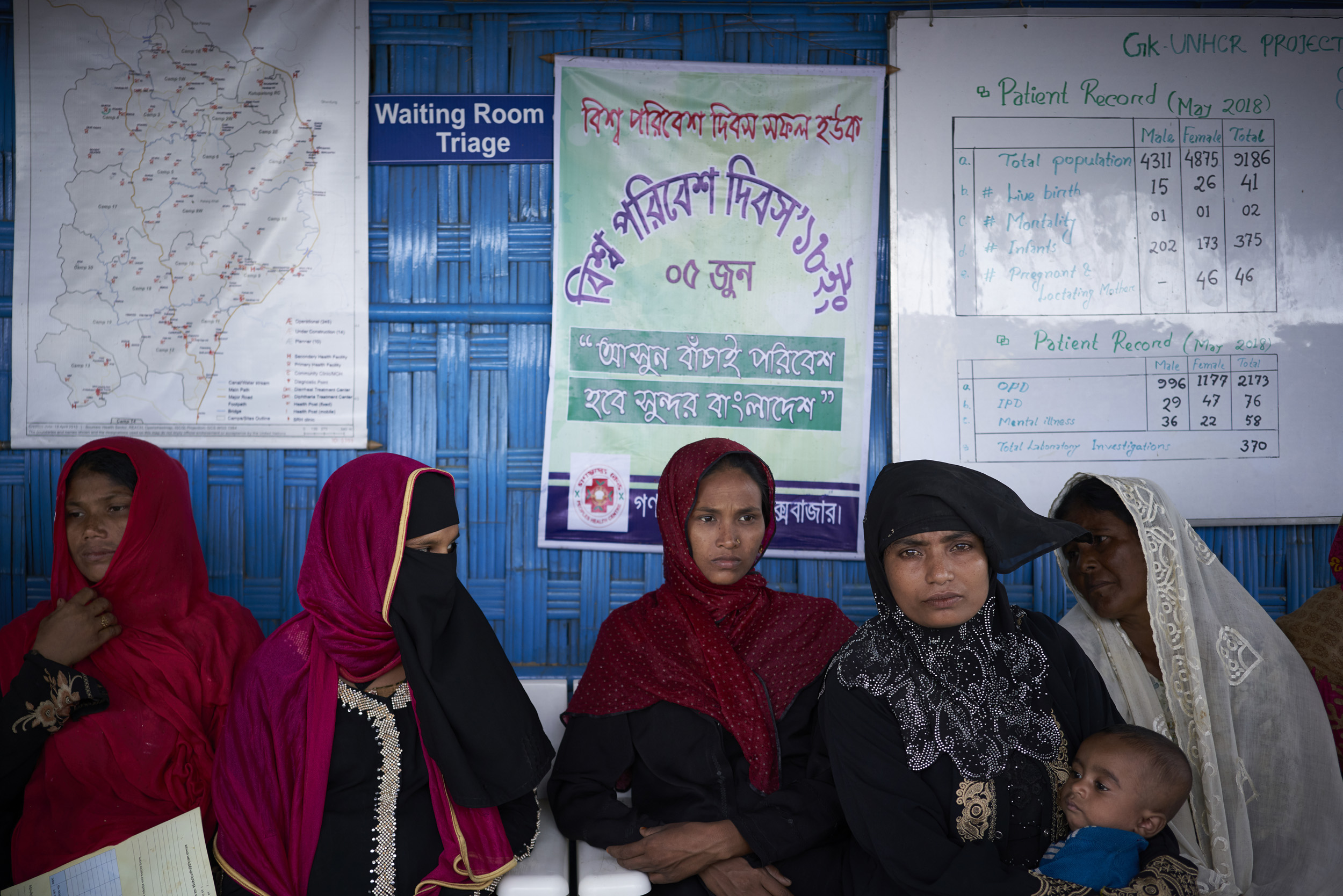 Rahana Begum, 30, second from right, holds her three-month-old infant Rokia, as she waits to be seen by a healthcare professional at the UNHCR primary health care clinic in Camp 4, Kutupalong Expansion Site for Rohingya refugees, Ukhia, Cox's Bazar District, Bangladesh.