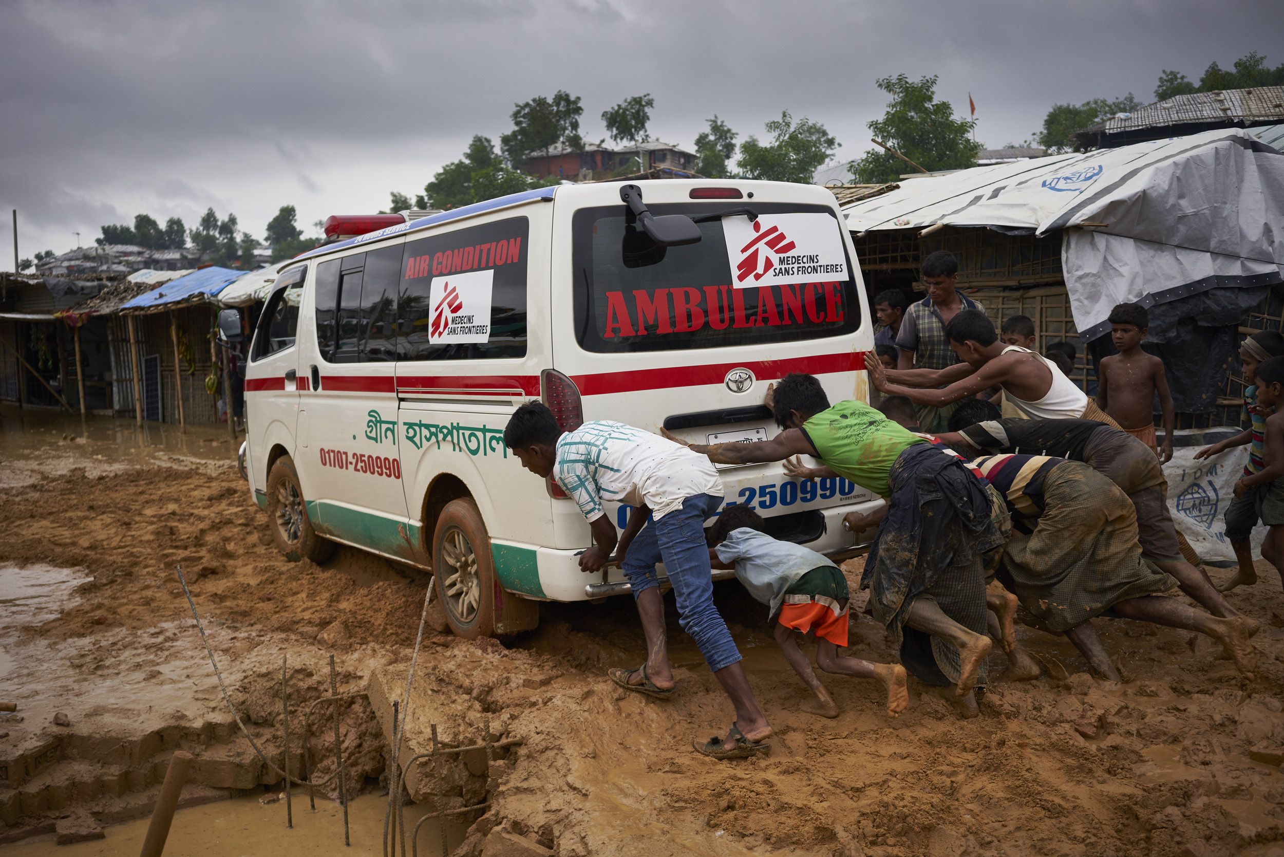 Rohingya refugees help push an ambulance stuck on a road damaged by heavy monsoon rains in Kutupalong Expansion Site for Rohingya refugees, Ukhia, Cox's Bazar District, Bangladesh.