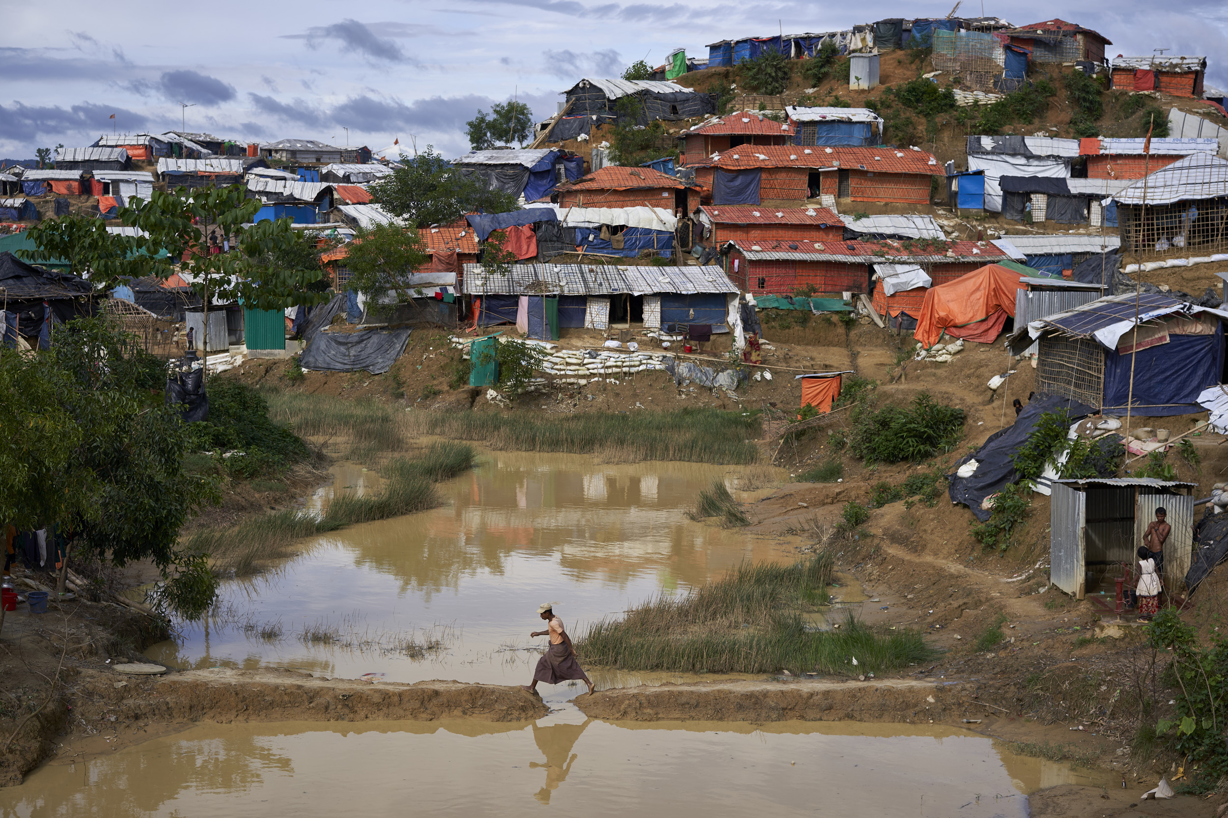 A Rohingya refugee crosses a body of water next to shelters set on a hill in Balukhali settlement for Rohingya refugees, Ukhia, Cox's Bazar District, Bangladesh.