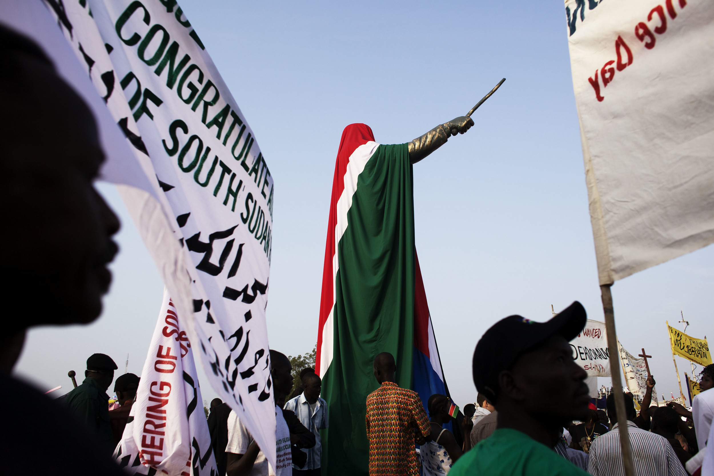 People gather around a statue of former Southern Sudanese leader John Garang, draped in the national flag of South Sudan, during independence celebrations in Juba, South Sudan, Saturday, July 9, 2011. (AP Photo/David Azia)