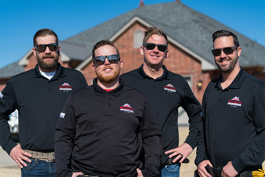 Elliott Roofing team standing outside of a residential home