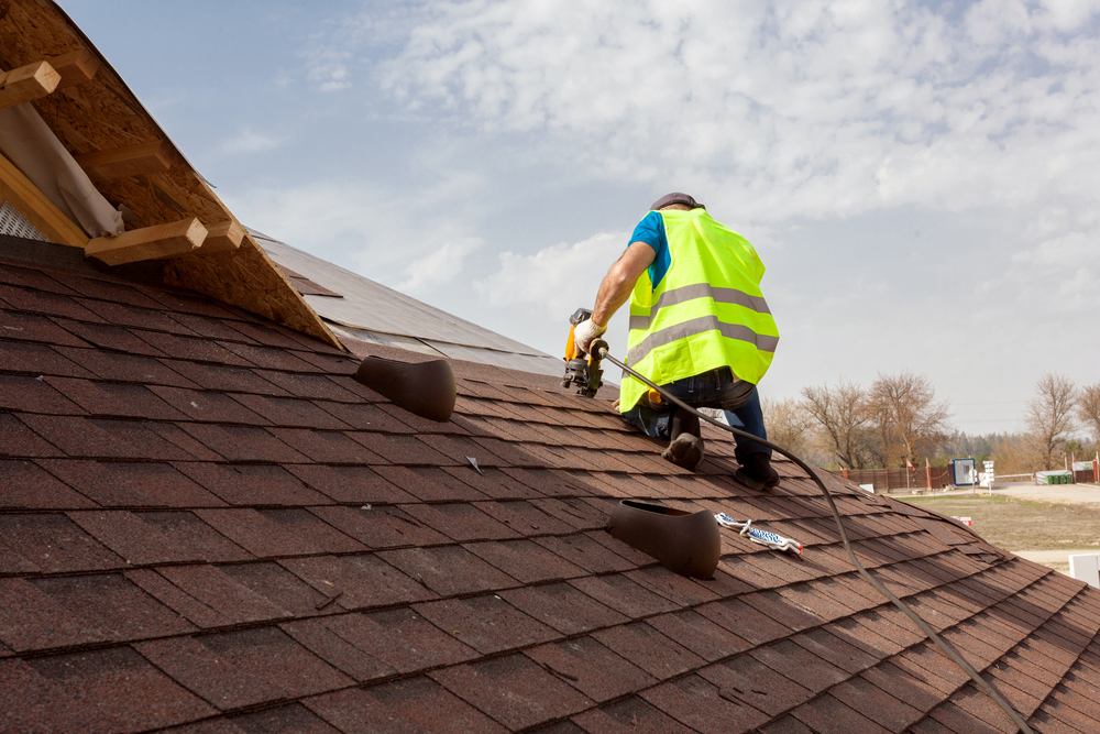 A roofer repairing a roof top
