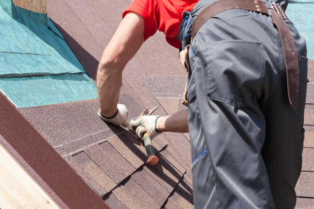 A roofer setting the shingles