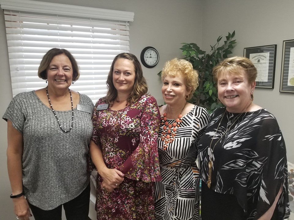 From left, Mutual Ground Board President Andi Danis and Executive Director Michelle Meyer pose with retiring Breaking Free Executive Director Teddi Krochman and Board President Cindy Heibel on Friday after signing paperwork bringing the two longtime social service agencies together.