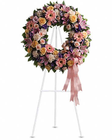 Graceful Wreath    A mix of flowers such as peach roses, gerberas and carnations, pink asiatic lilies and lisianthus, purple limonium and lavender larkspur nest in greens on an easel-mounted wreath.    Shop Now>>