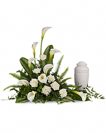 Stately Lilies    A calming portrait in ivory. Majestic calla lilies and stately white roses are framed by the lush leaves of aspidistra and calathea. Soft green sword fern adds to the soothing tones. Large white calla lilies pair with white roses and lush greens that include soft, airy sword fern and glossy aspidistra. Please note: Arrangement does not include urn.    Buy Now