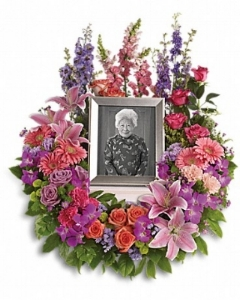 In Memoriam Wreath    Purple orchids and asters, orange, dark pink and lavender roses, pink and peach carnations, lavender larkspur, green chrysanthemums, and a range of pink blooms including oriental lilies, gerberas, snapdragons and more.    Buy Now>>