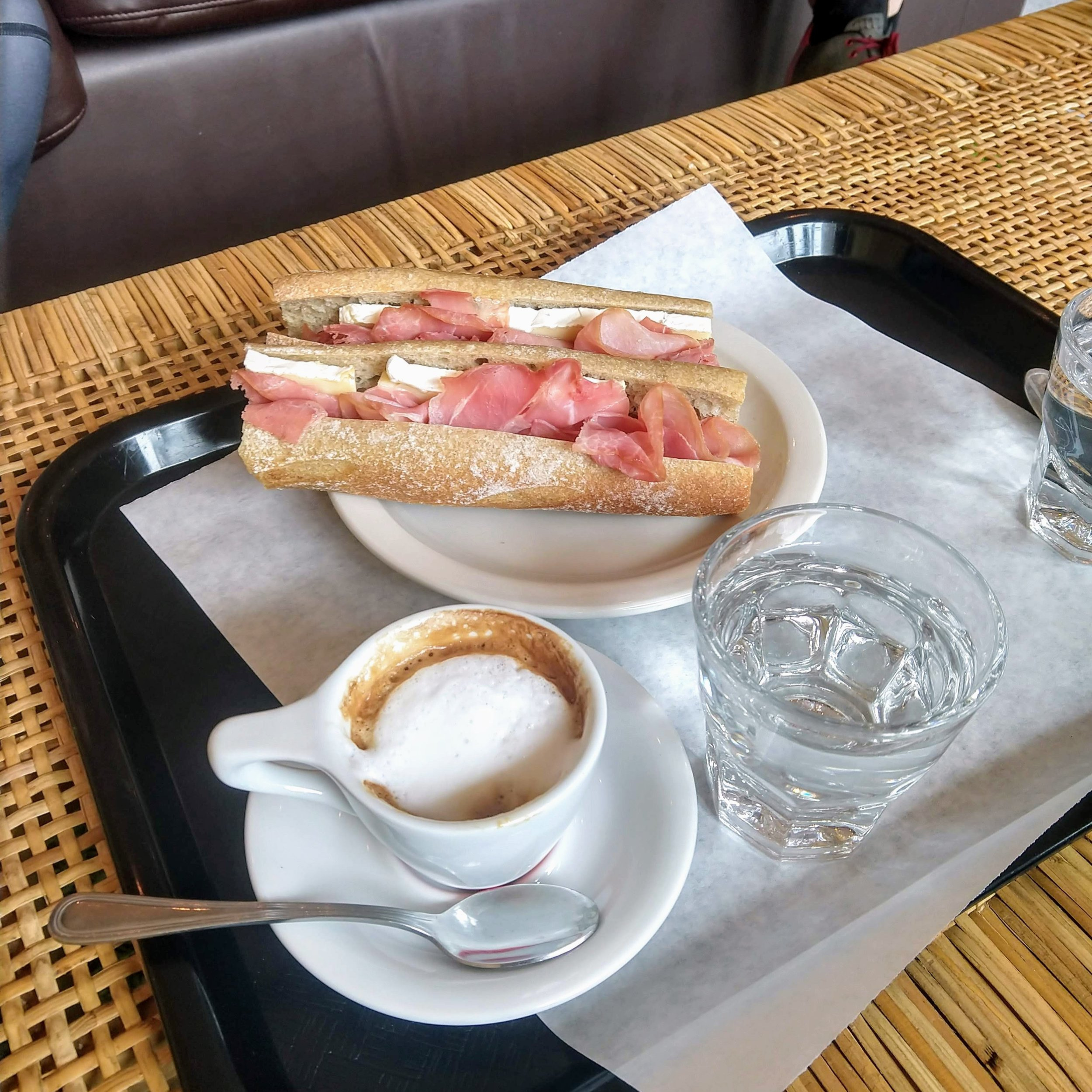 Hot cortado and baguette with ham and brie.