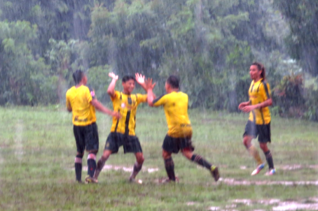 Balgue FC celebrating their goal in the rain in their Selvista sponsored shirts