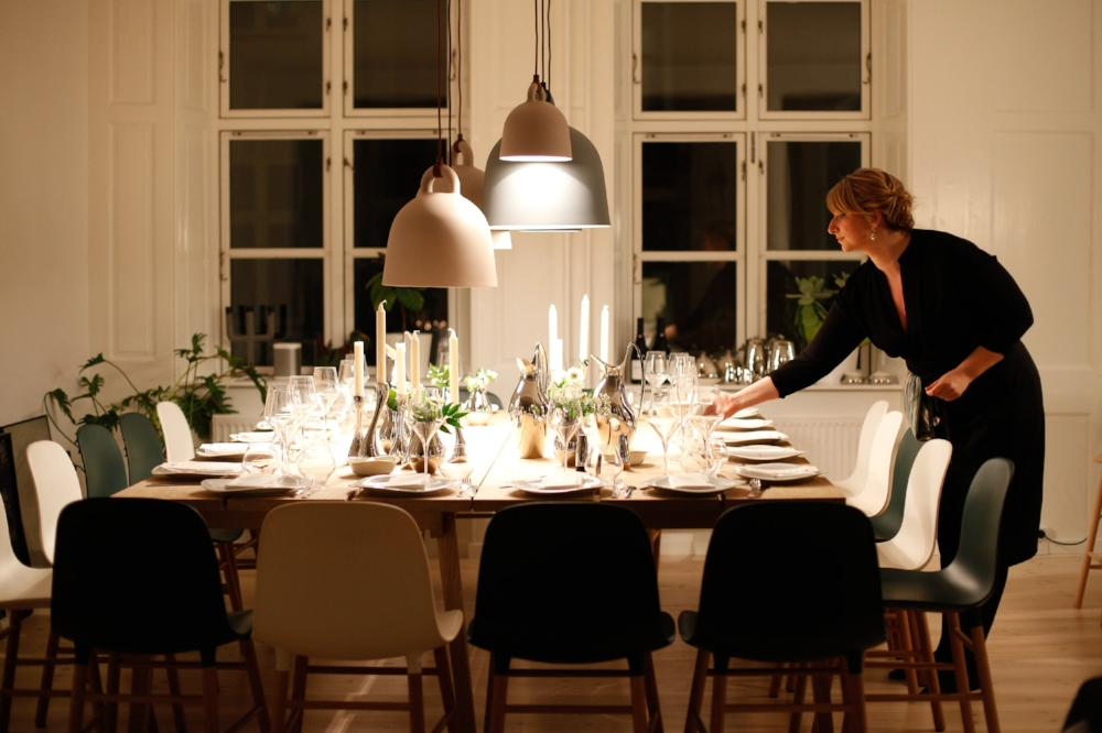 Woman lights candles on dinner table before dinner party