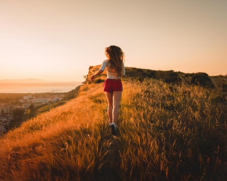 Young woman running in field at sunset