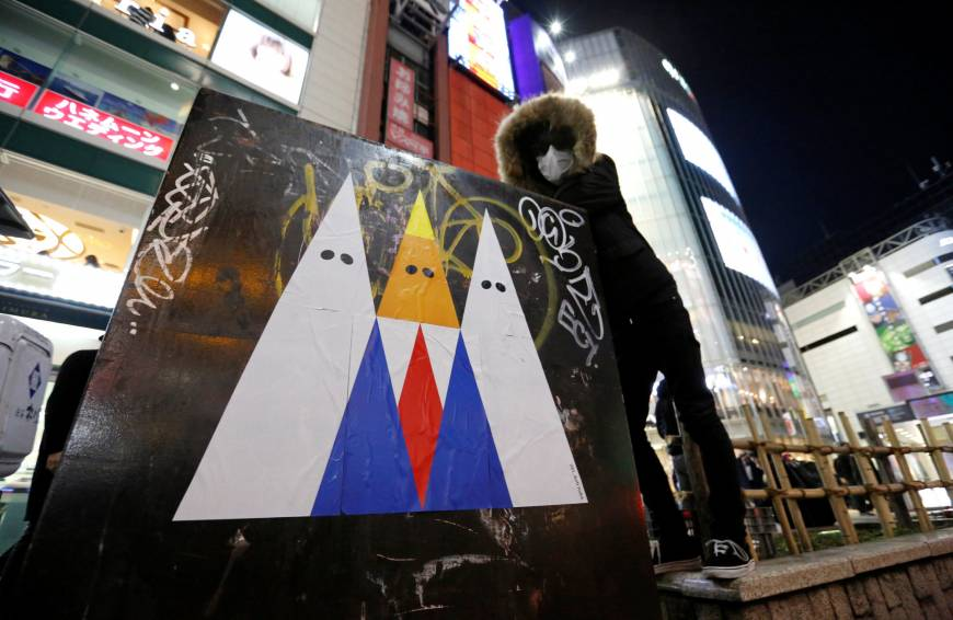 A graffiti artist known as 281_Anti Nuke poses for a photo next to an example of his recent artwork depicting U.S. President Donald Trump, in Tokyo's Shibuya district on Friday.