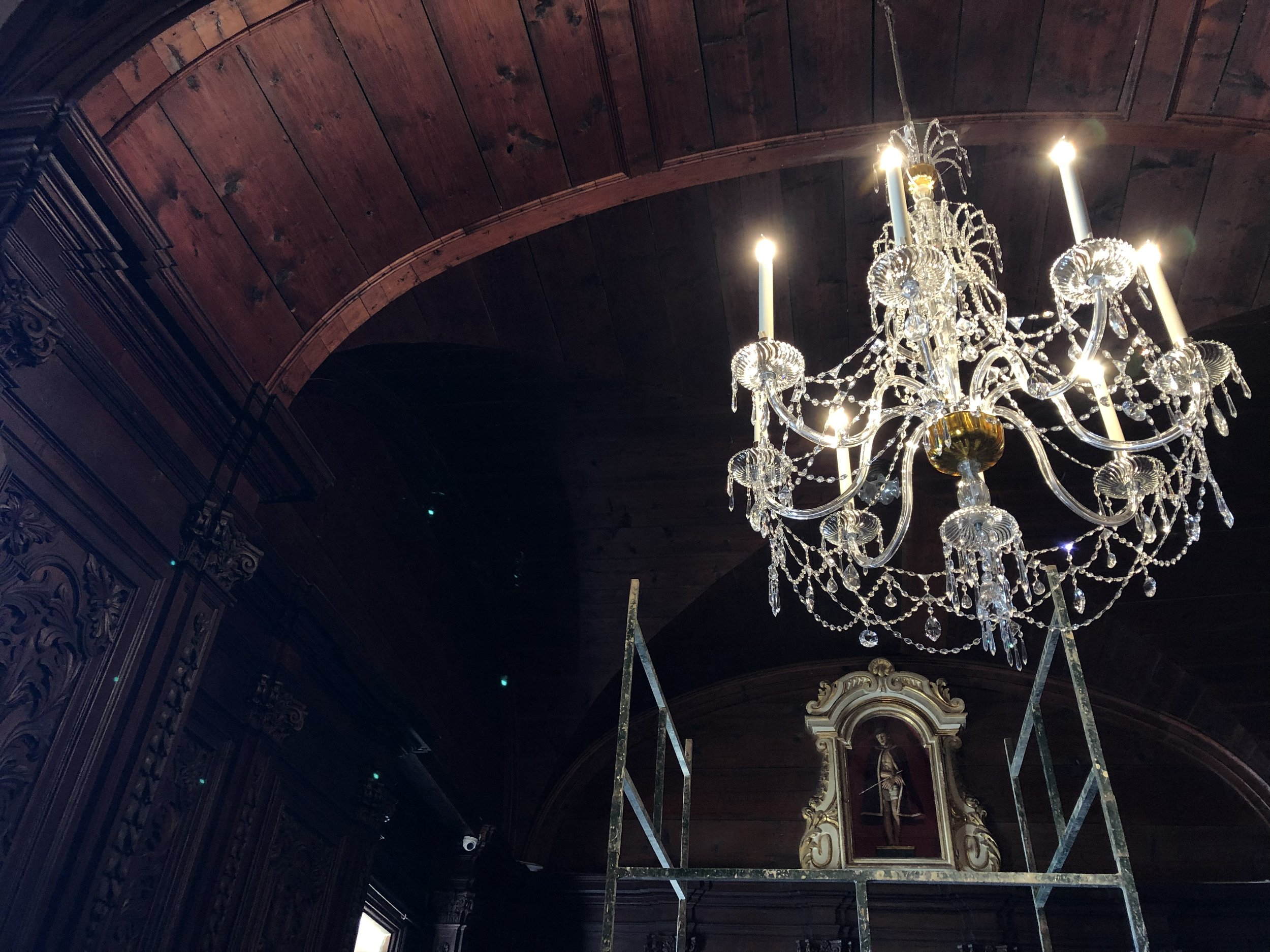 The lit up chandelier against the wood panelling of the sacristy