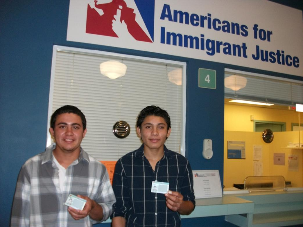 Brothers who arrived as unaccompanied minors smile as they receive their green cards.