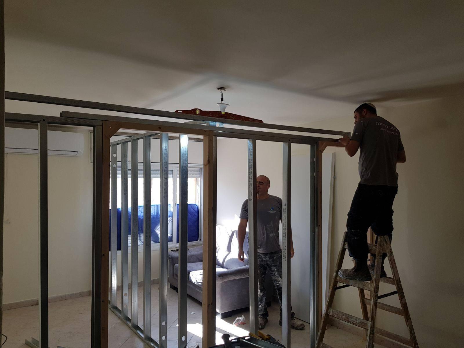 Tenufa Bakehila workers rebuilding a home in Israel.