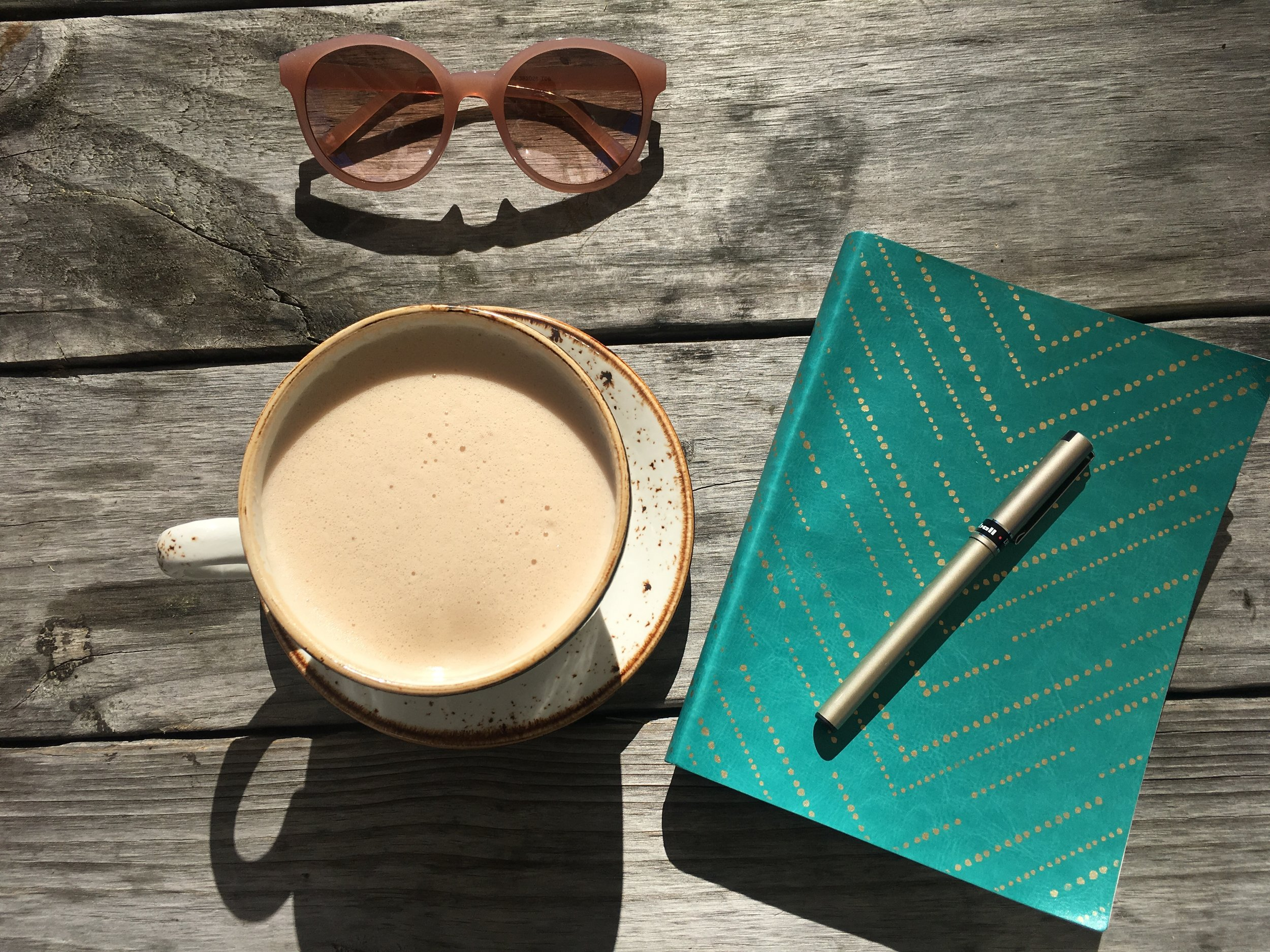 Sunglasses, Chai tea, notebook and pen on wood table