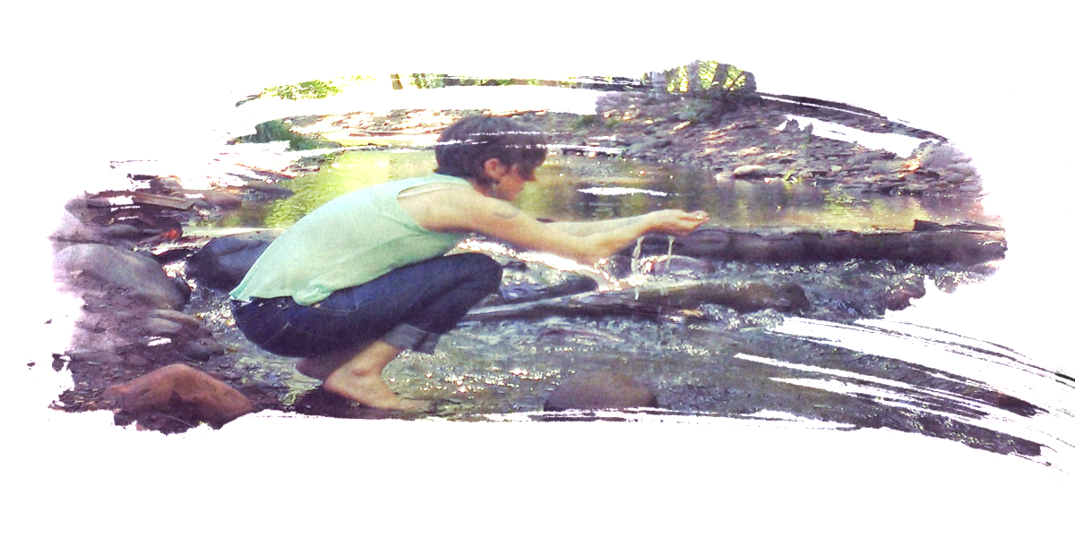a pic of me a white non binary short haired person kneeling at a streams edge with out stretched and cupped hands letting water run through wearing a light blue tank top and dark jeans whith no shoes on