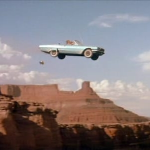 a light blue car heads off the grand canyon to its doom with a beautiful blue sky behind
