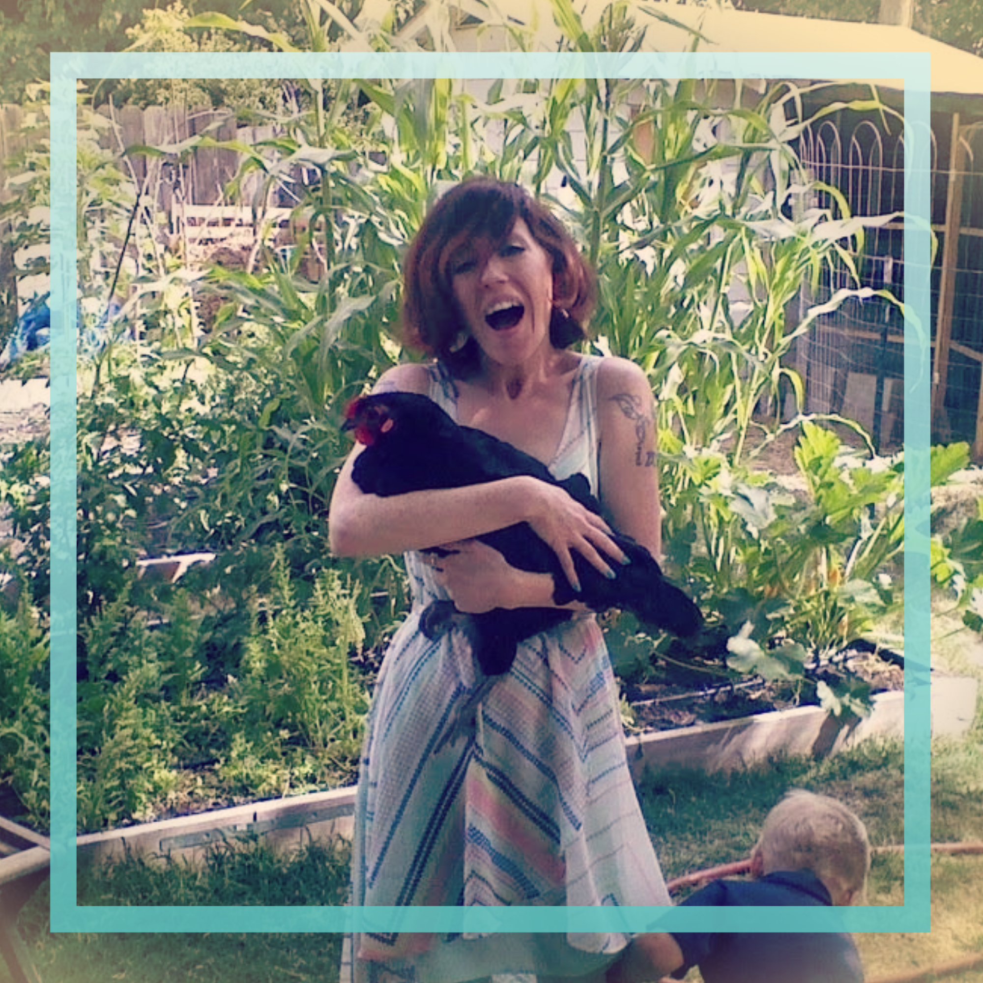 a square pic of me a white nonbinary with shoulderlength red hair in this picture and wearing a white and blue striped summer dress holding a chicken in a firends garden while yelling something so my mouth is wide open and there is lots of tall green corn stalks in the background an odd photo I know nut i love it