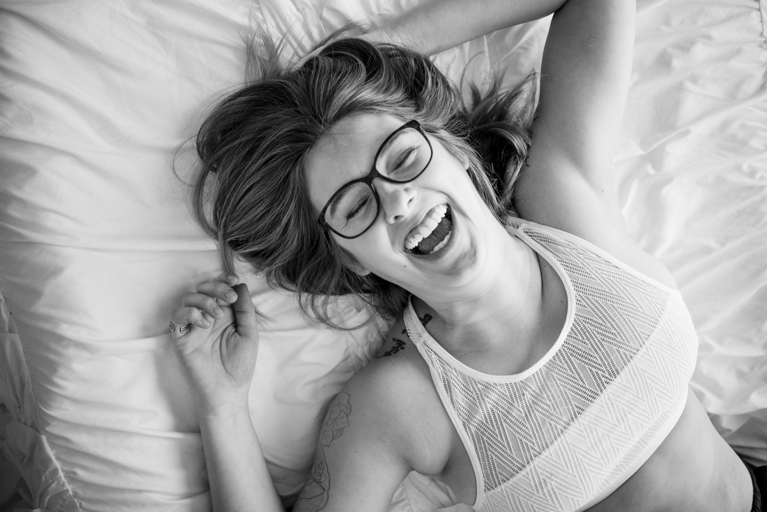 black and white boudoir of Toni laying on the bed laughing