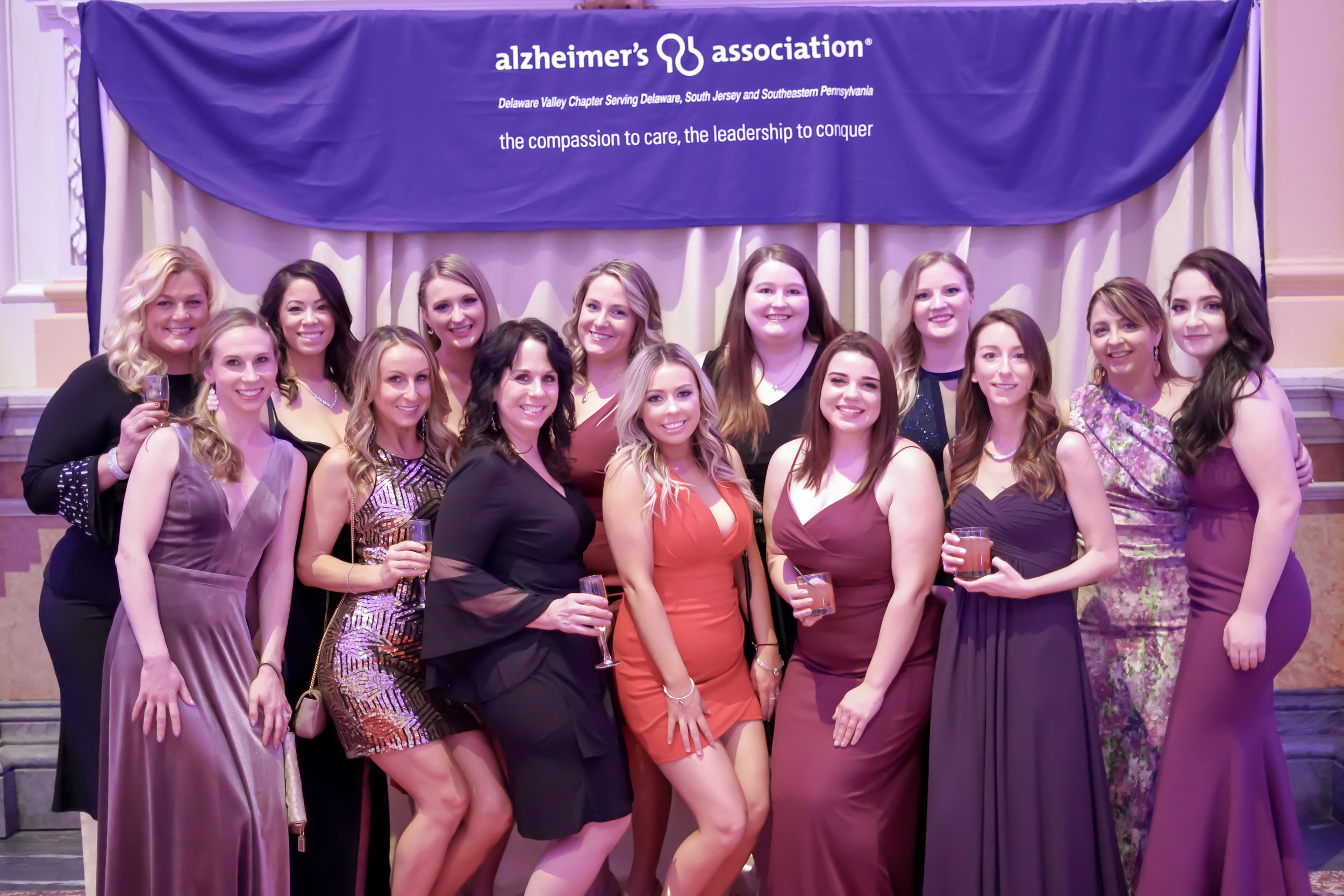 large group of friends pose for step and repeat at party in purple event