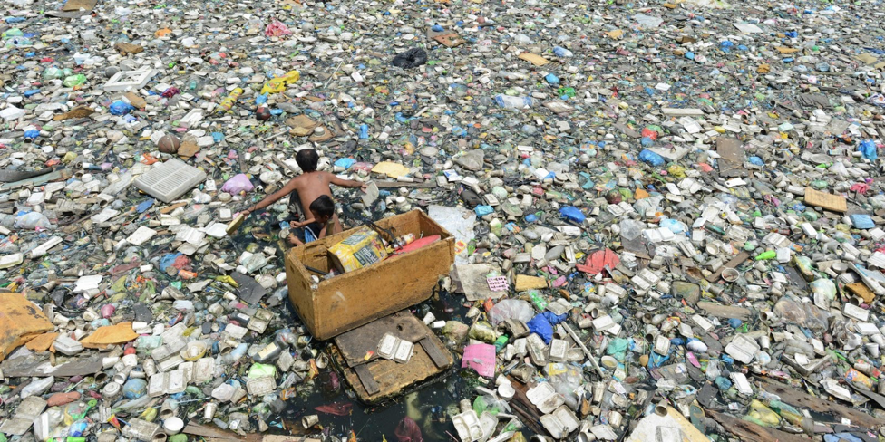 Family in Manila sorts through plastic to sell to junkshops.