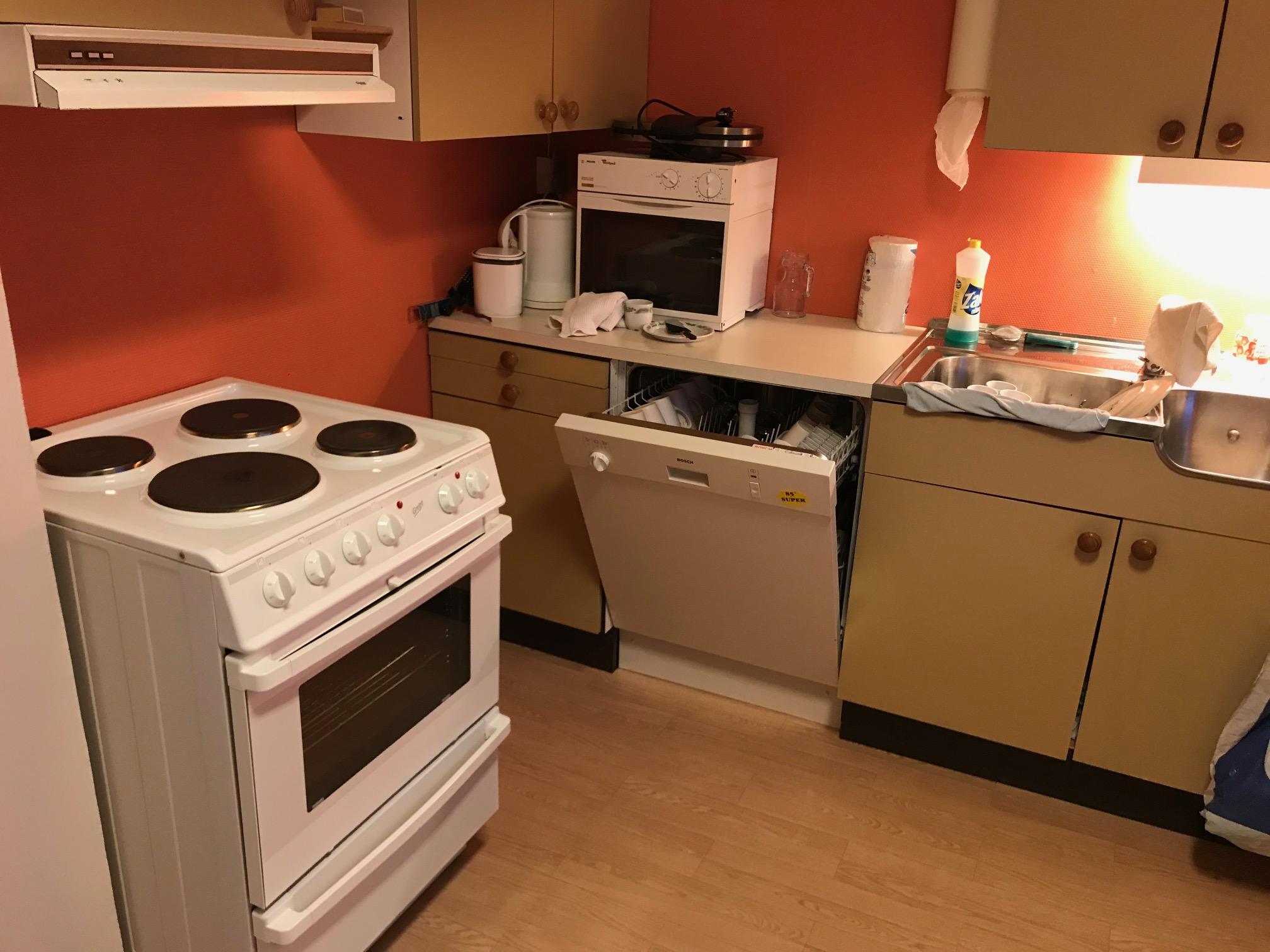 Et enkelt kjøkken med det som trengs av utstyr og dekketøy. Og forresten; det er også en mikroovn der.