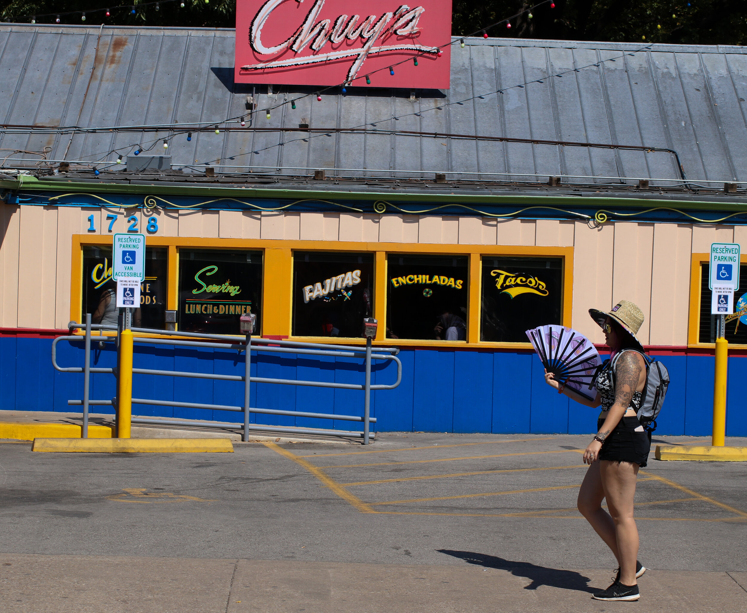 An ACL reveler passes Chuys with an ornamental fan