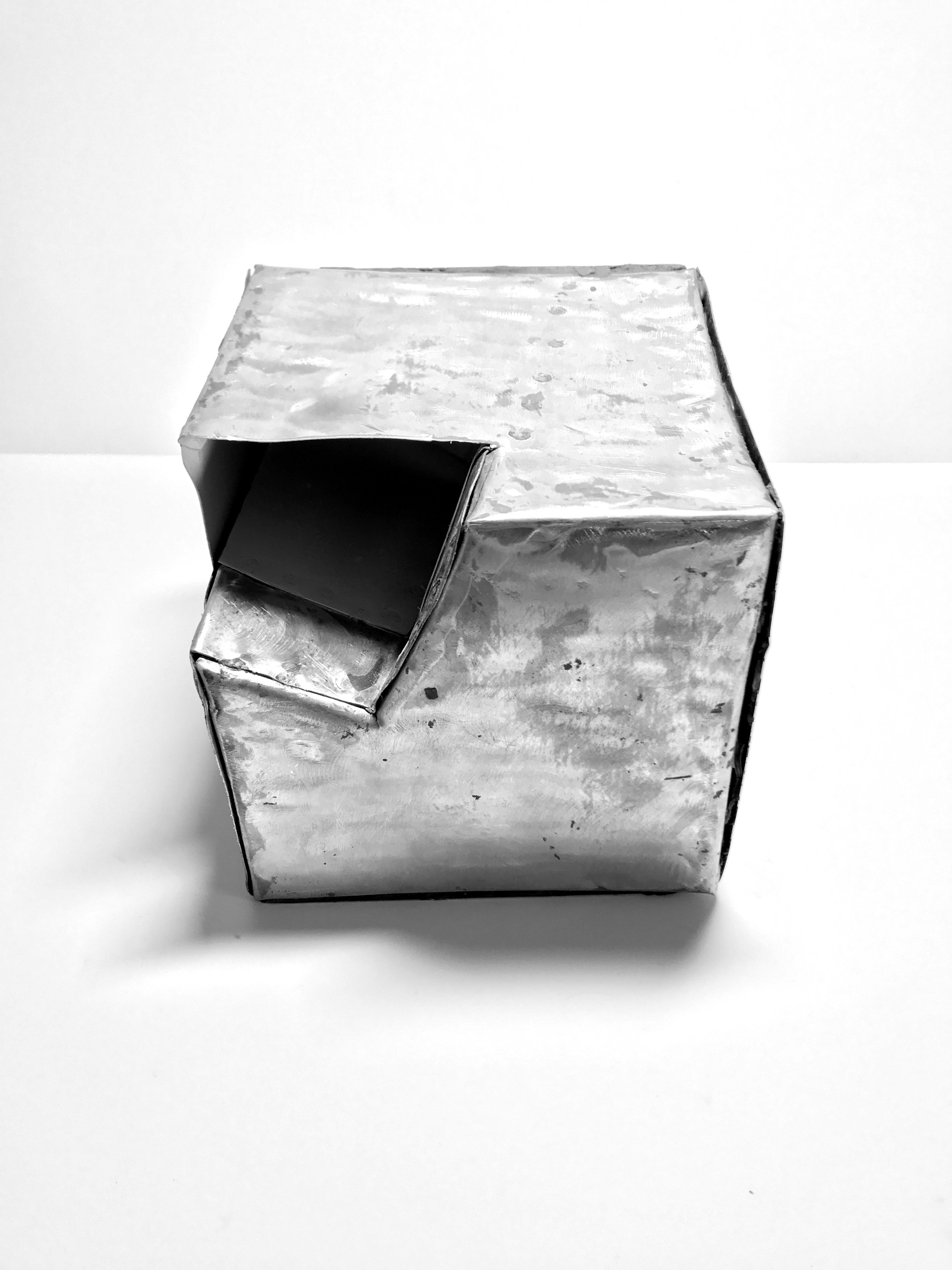 """CUTTING PLANES Cut planes perpendicularly on a slanted axis. Overlap cuts from different sides to create reliefs in the cube.   SEAMS Used only lap seams to not complicate the design which already draws attention to the reliefs made by the intersecting cuts.   COLOR  White used on the """"interior"""" of the object to draw the viewer in."""