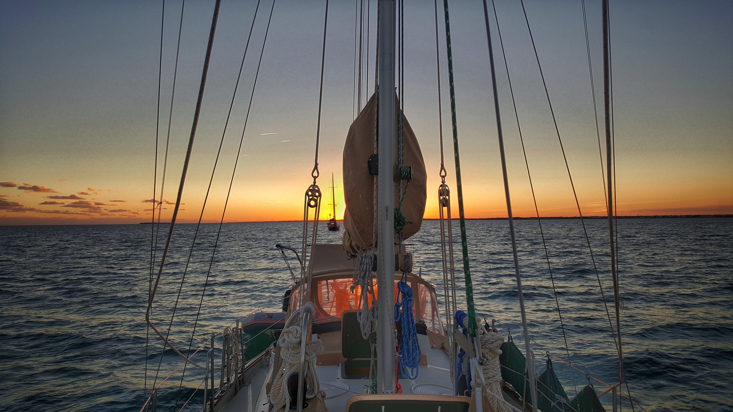 Anchored at Rodriguez Key, just off of Key Largo, in the Florida Keys; the orange glow in the dodger window is a reflection of the setting sun in the clear vinyl panel