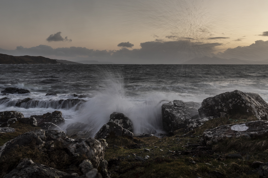 A stormy Tarskavaig Beach at sunset with waves crashing on the rocks