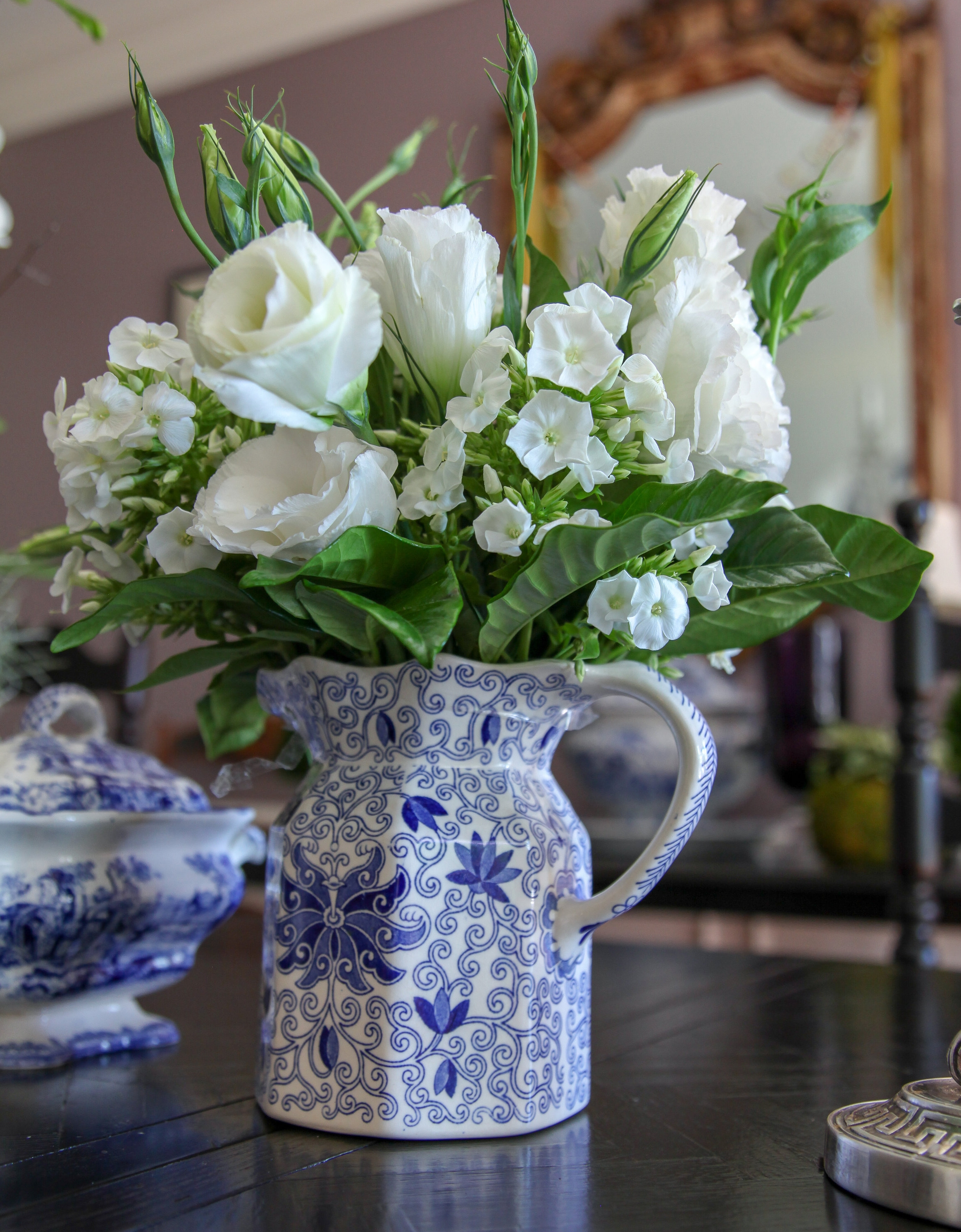 An antique English milk pitcher makes a tidy receptacle for a white and green floral arrangement.