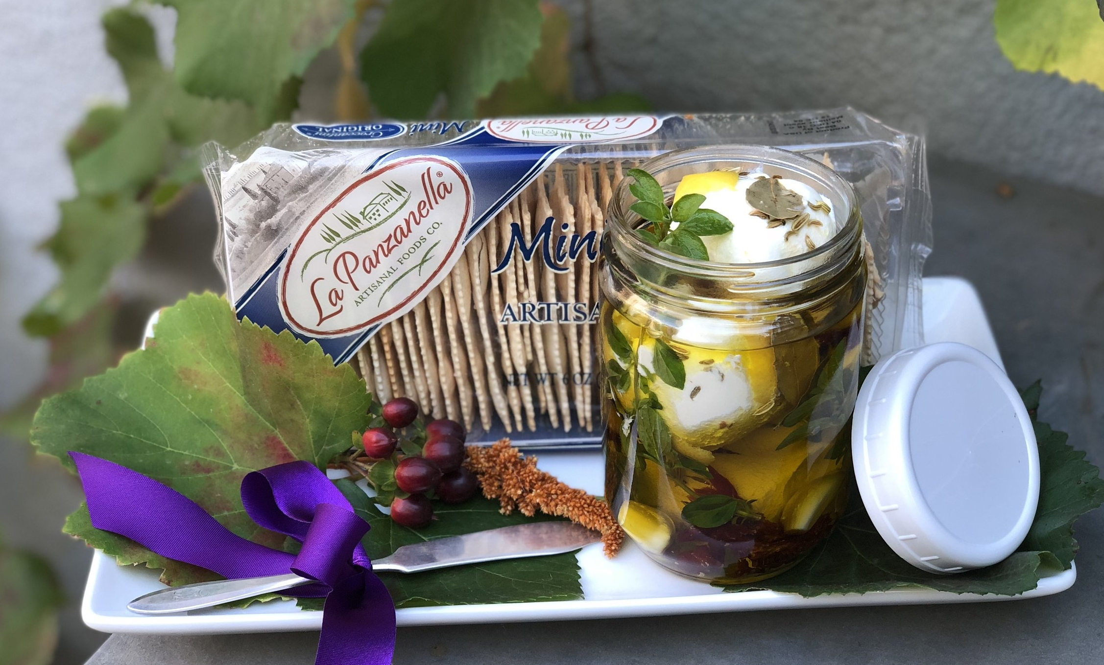 Assemble Marinated Goat Cheese on a simple tray, artisan crackers and a vintage butter knife.