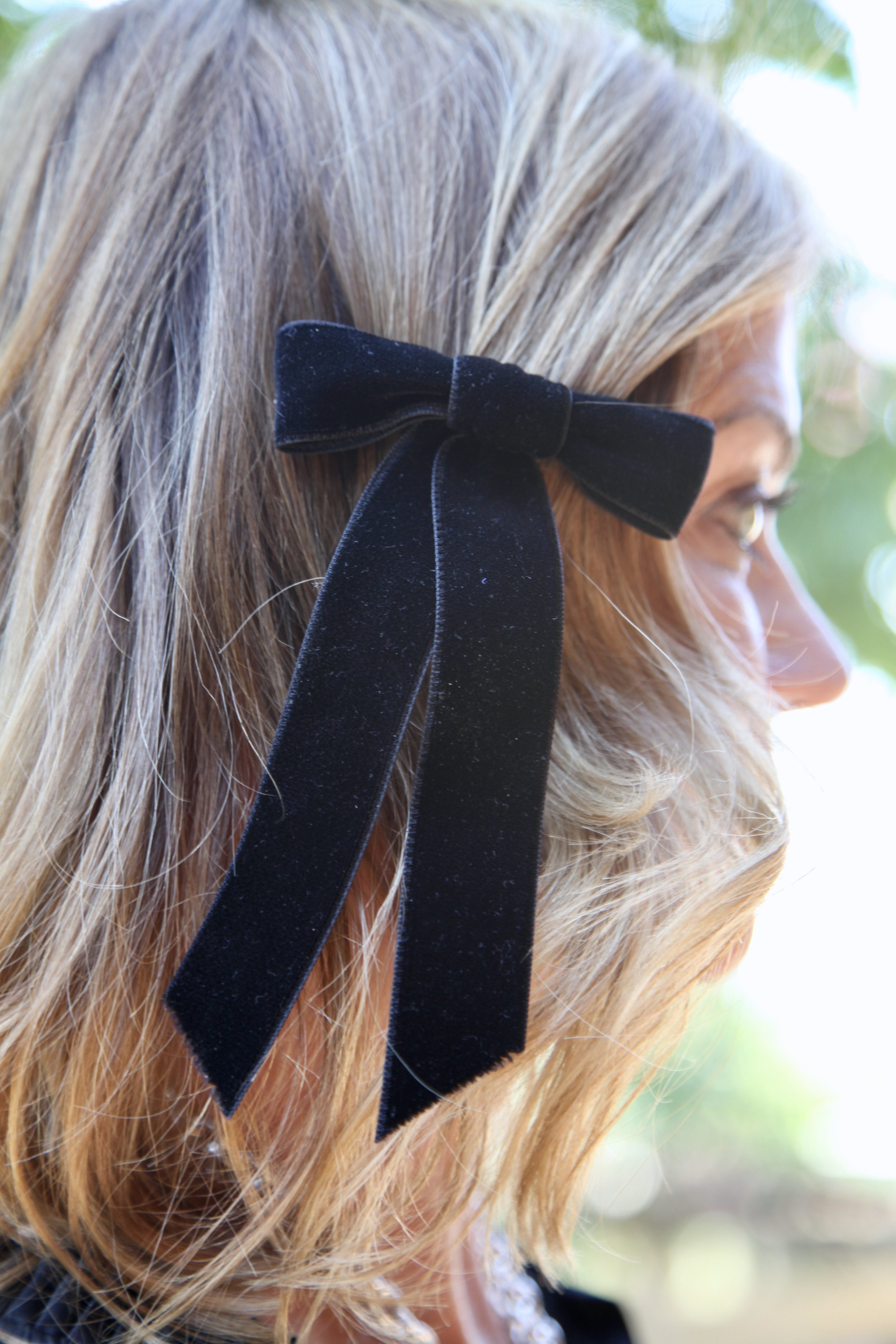 Pull back bangs with a small velvet bow or tie your hair away from your face with a simple twist.