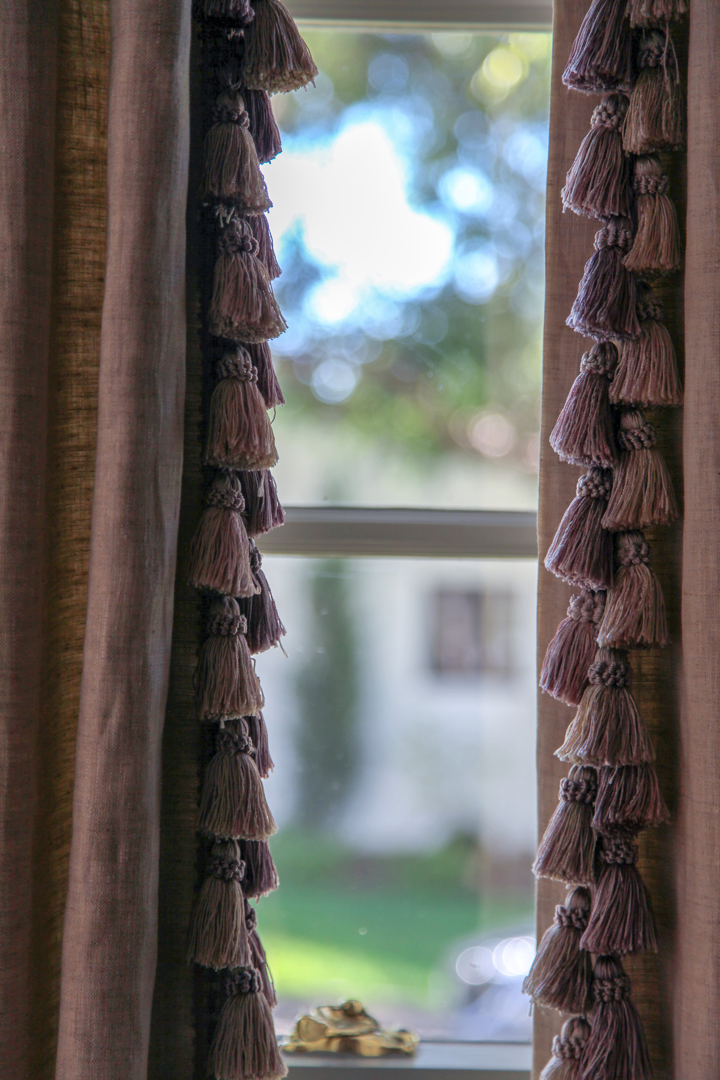 Here purple linen drapes are fringed with tassels in varying shades of purple.