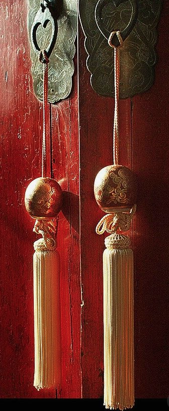 Chinese inspired tassels made with gold silk threads add that final touch to an already stunning door.