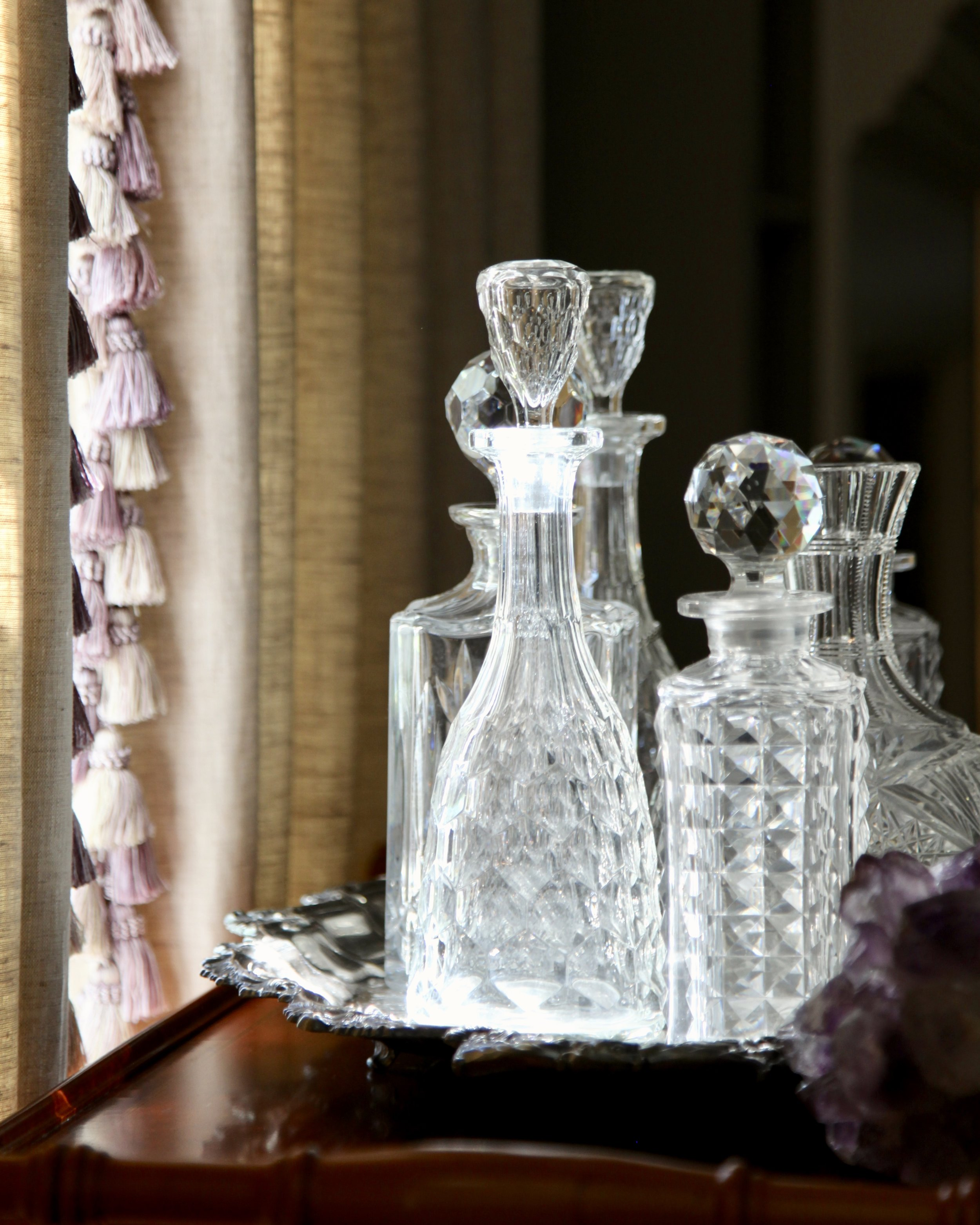 Antique crystal decanters are arranged in groupings. When not is use, they're fine to display without liquids. Their facets expose their beauty.