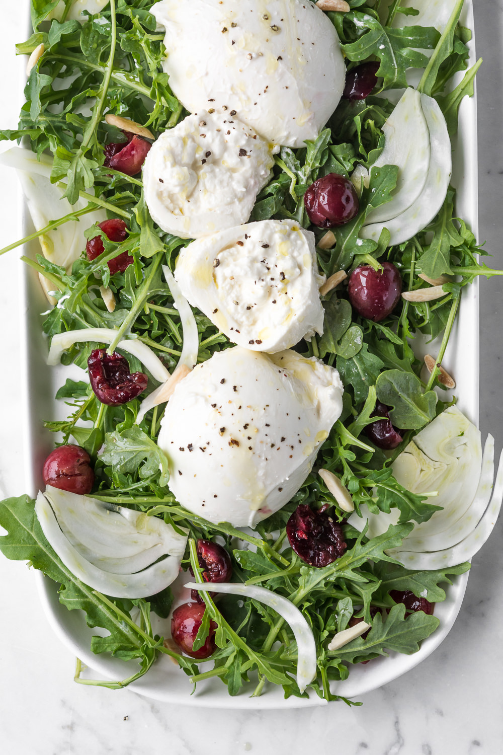 arugula salad with pickled cherries, burrata, fennel and almonds