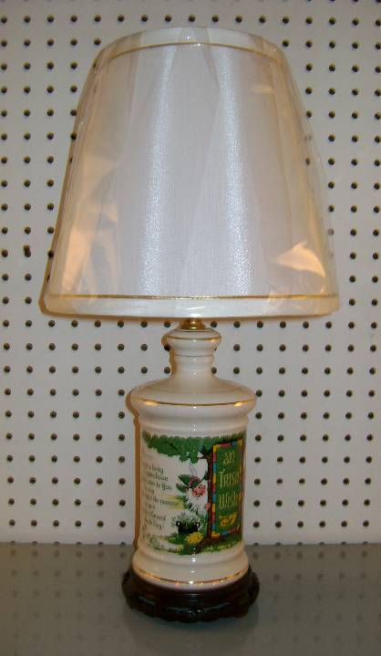 """Irish Whiskey Decanter Lamp    """"An Irish Wish"""" designed whiskey crock has been turned into a very colorful lamp.    Stands 19"""" high. Shown with a #104 Eggshell Silk lampshade with gold edge trim.    $165.00, plus shipping"""