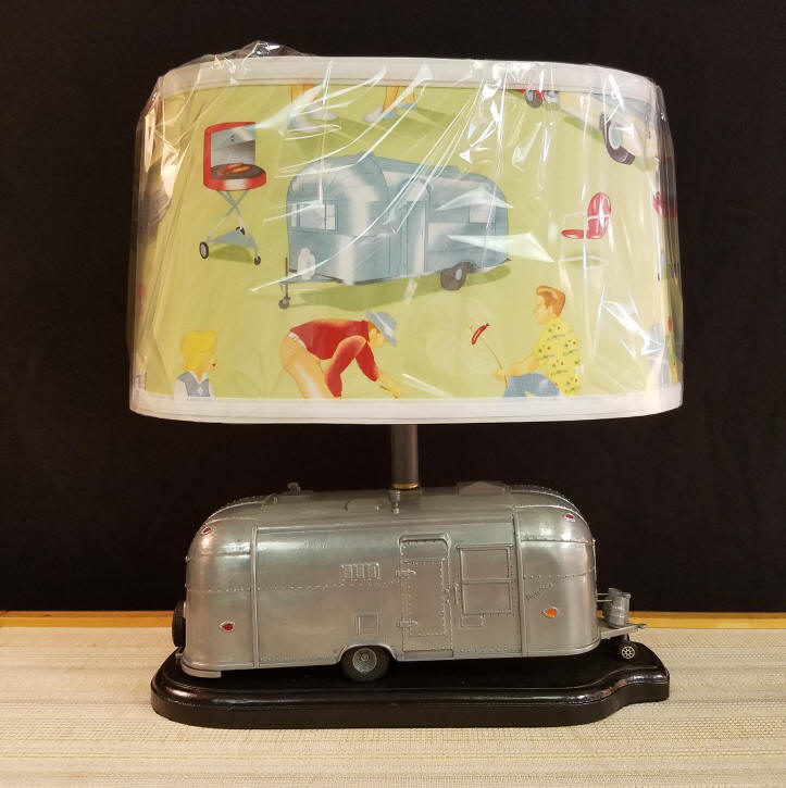 """Die-Cast Airstream """"Flying Cloud"""" Camper Lamp    This die-cast Airstream RV / Camper is a retired piece that was sold by Pottery Barn. We have transformed it into this must-have lamp for any camping enthusiast. Since we make all of the lampshades we sell, we purchased this reproduction vintage camping themed fabric for the shade. Buyer may request traditional shade, if desired. It stands 15"""" tall, including the lampshade & is 14"""" wide. Great size for any location, maybe even your Airstream Travel Trailer.    $250.00, plus shipping"""