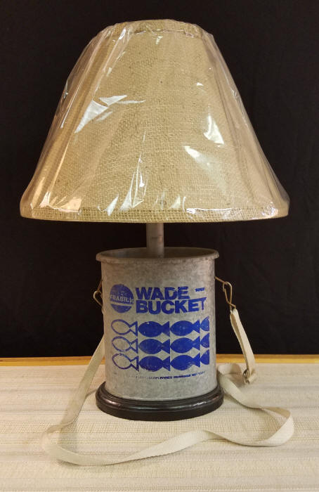 """Vintage Wade Bucket Fishing Lamp    This Vintage Frabill, Oval Galvanized Wading Bucket makes the perfect lamp for the fisherman in your family. Includes the original strap that can easily be removed, if desired. It stands 18-1/2"""" tall, including the lampshade.    $150.00, plus shipping"""