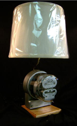 """Duncan Electric Meter Lamp    This Lamp is made from an Antique working electric meter. With the 3-way switch, you can see the speed of the dial increase as you switch the light bulb from low, to medium, to high. Designed with an Oak Wood Base. Really cool! Stands 21"""" tall, including the lampshade.    $285.00, plus shipping"""