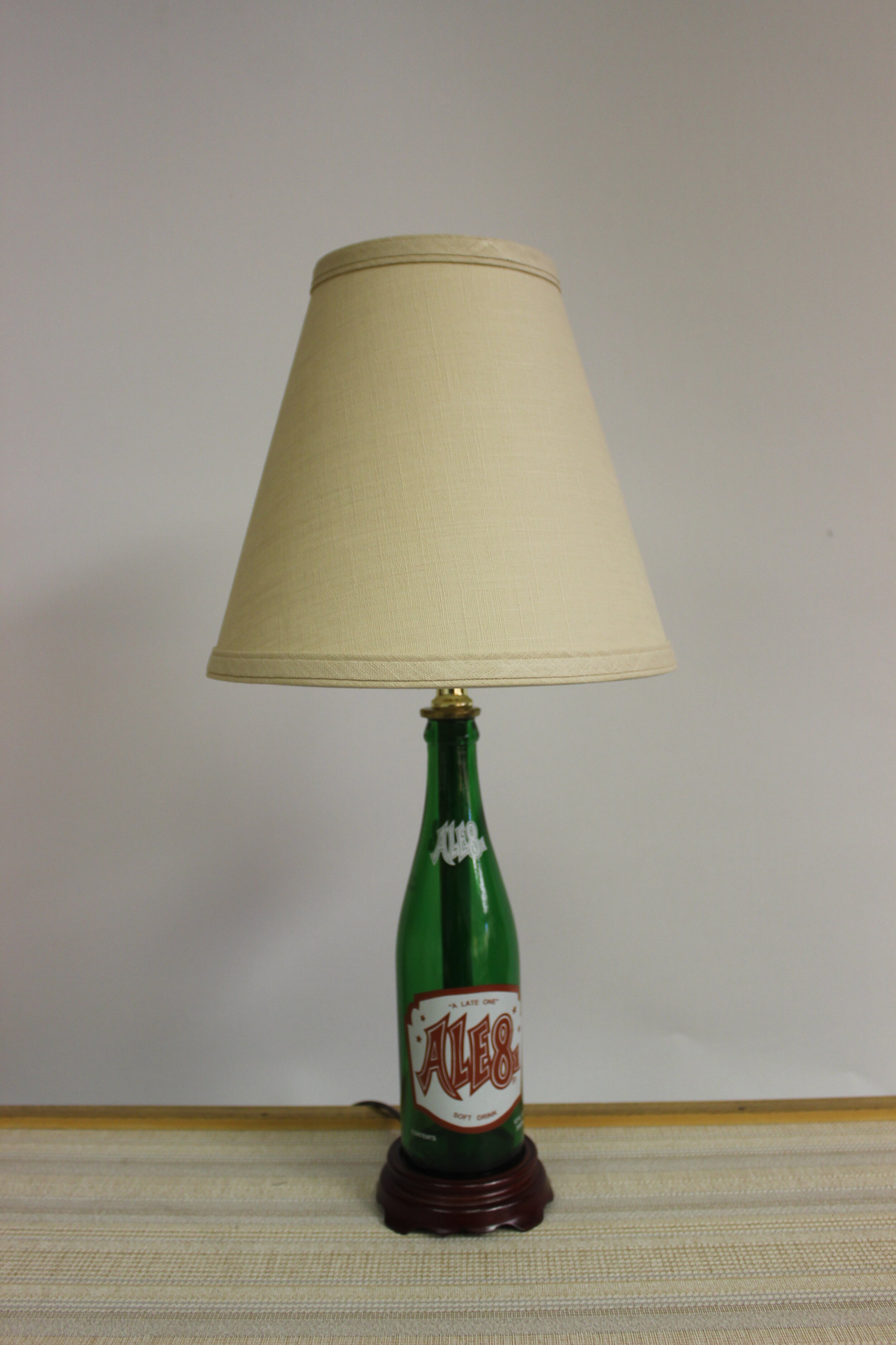 """Ale-8-1 Soda Bottle Lamp    Ale-8 is a regional soft drink bottled in Central Kentucky    The lamp is wired with high quality electrical components, including a Leviton lamp socket. Brown lamp wire extending approximately 7 feet from the wood base to the plug.     This lamp stands 19"""" high.    $125.00, plus shipping"""