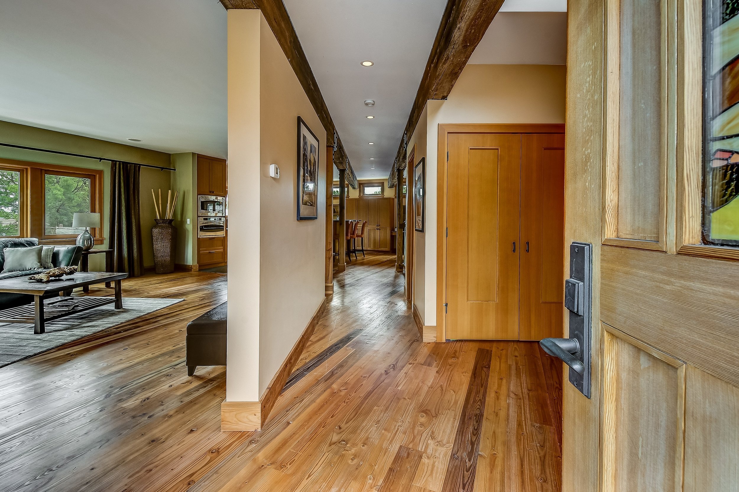 The custom stained glass door and striking reclaimed Tresslewood floors and beams offer a warm welcome.
