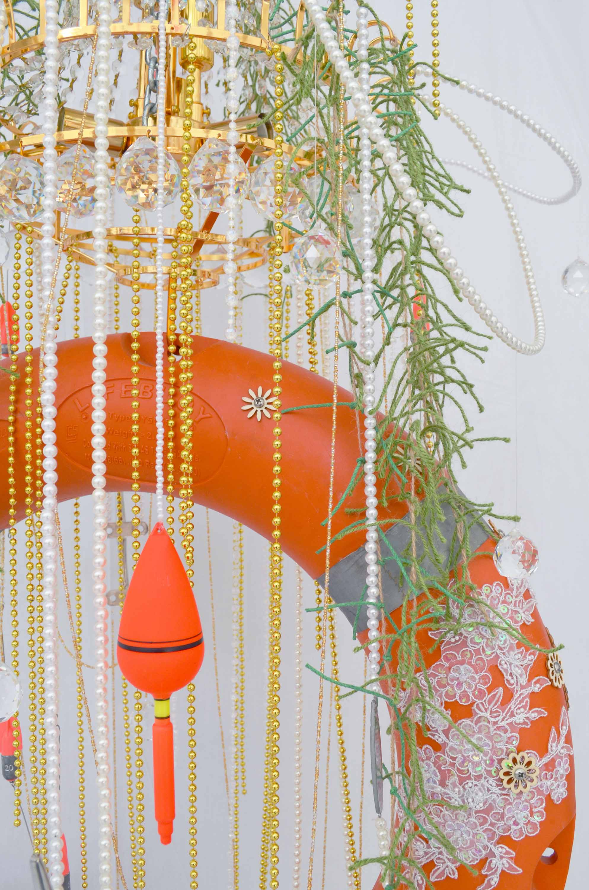 Khairullah Rahim, 'Silly Enamour' (detail), 2019, chandelier parts, Salvzburg travel guide collage on boat steering wheel, assorted faux pearls, metal hook, lifebuoy, boat cleat, propeller, fishing lure, sequined lace trim, laser cut wood, screw, chain, truss, concrete, silk flowers, 200 x 200cm. Image courtesy of the artist.