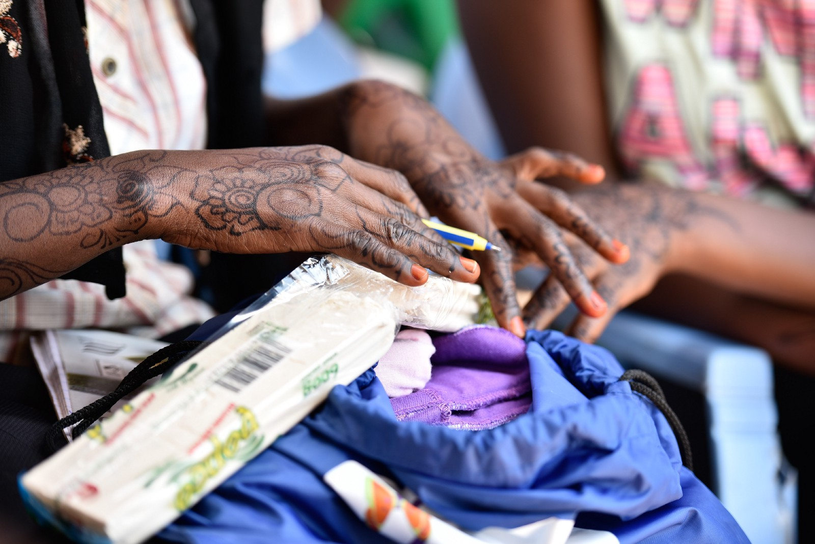 A young woman perusing her 'Huru Kit' containing reusable sanitary pads