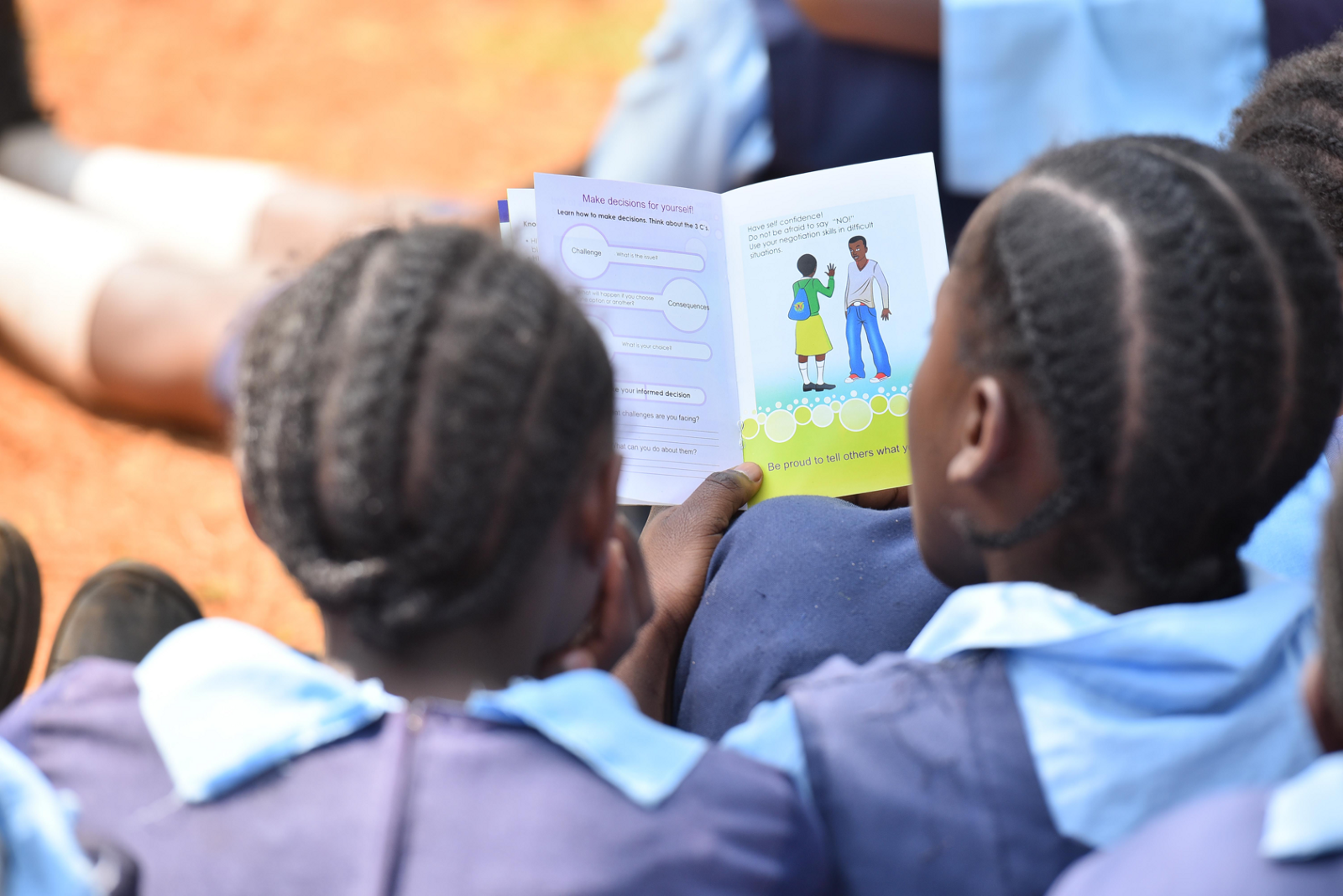 Girls reading a Huru educational booklet during a distribution